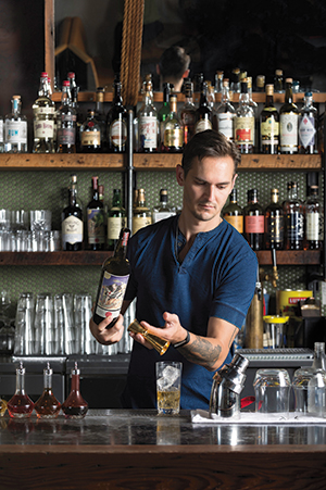 Opposite: Chris Lane uses tools from Umami Mart as he mixes a drink at Oakland's Ramen Shop.