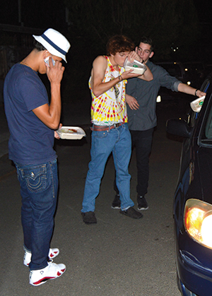Hungry teens meet a SpoonRocket driver at the curb. (Photo by Jack Pertschuk)