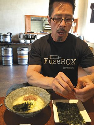 Chef Chang crumbles seaweed to add to his soup. (Photos by Anna Mindess)