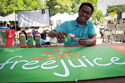 """uicer in Chief Perrin Clark pours samples at Berkeley's Live Oak Park Fair. Clark says Bay Bucks was a """"business booster"""" for Free Juice."""