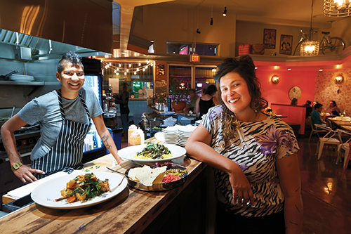 Chef Preeti Mistry, left, of Juhu Beach Club, plates food from Feral Heart Farm that waiter Bassin, right, grows and serves.