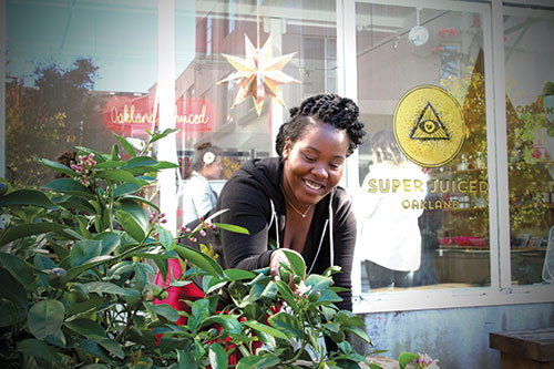 Sundara Englin, who started as a Super Juiced intern and was promoted to assistant manager, picks limes and herbs for drinks from the garden at Swan's Market.