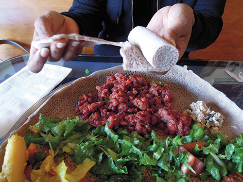 At Café Colucci, her Ethiopian restaurant in Oakland, Fetlework Tefferi demonstrates how to rip off a piece of injera to gather up a bite of vegetables or meat.