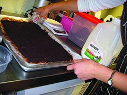 Gallardo prepares a finely ground mix of hand-sourced, organic cacao nibs, cinnamon, and sugar, the base for her hot chocolate.
