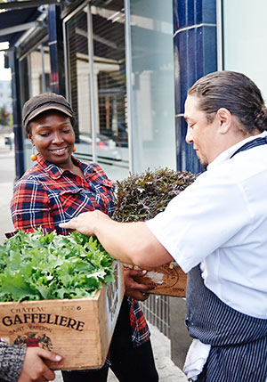 WOW farm manager Kana Azhari (left) and a WOW intern deliver produce to Flora chef Rico Rivera.