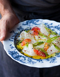 Chef Charlie Hallowell of Penrose holds a plate of local halibut crudo with blood oranges, snap peas, garlic sprouts, and Aleppo pepper.