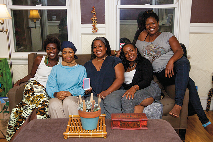 Rooted in friendship: Rootical Gathering members (left to right): YaVette Holts, Kweli Session, LeRhonda Birden, Karen Gordon-Brown, Noni Session. Two members were out of town. The wooden box on the table holds the money collected at each meeting