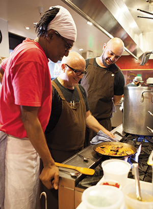 Line cook Robert Edwards (left) and sous chef Sean Brekke-Miesner (right) confer with Canales on the fideuà