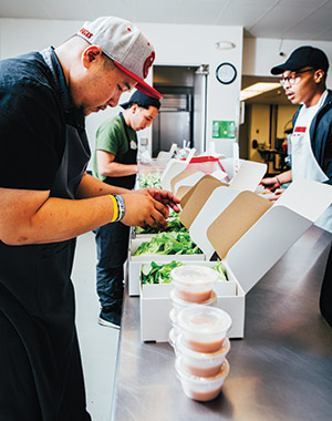 Chef Jefferson Sevilla (at left) and youth employees Roger Davalos and Rashawn Moore (at right) finalize preparations for the day's lunch deliveries