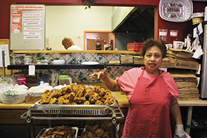 Laura Muñoz packs up Filipino favorites and lots of broasted chicken on a busy Saturday at Maharlika Restaurant on Thornton Avenue. (Photo by Cheryl Koehler)