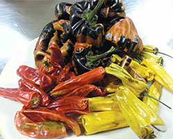 Chilhuacle negro chiles in the background. Foreground, the costeño rojo (red) and amarillo (yellow), two colors are variants of the same plant. All are important ingredients in moles. (Photo courtesy of Comal)