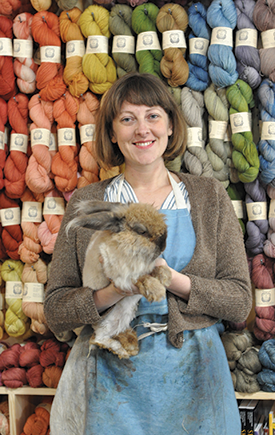 Kristine Vejar, owner of Oakland's A Verb for Keeping Warm, stands with her pet Angora bunny Marcel, in front of the store's line of Pioneer yarn, spun from Sally Fox's Merino wool. Marcel, who is also a fiber animal, lives in the dye garden behind the shop, where Kristine dyes the yarn herself. (Photo courtesy of Adrienne Rodriguez)