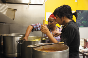 For the PK March dinner, Sirgut Badana (left) prepares Ethiopian stews much like those che cooks for customers at the Phat Beets Farmers' Market. She is assisted by PK organizer Kay Cuajunco.