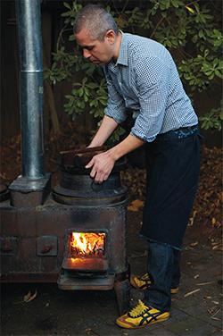 Sylvan Brackett tends a wood-fueled fire in a kamado oven. (Photo by Aya Brackett)