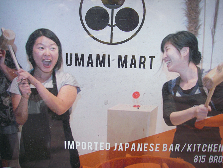 A poster hanging in the window of Umami Mart (photo by Erin Gleeson), shows proprietors Kayoko Akabori (left) and Yoko Kumano (right) pounding mochi at a pop-up event. (Photo by Kristina Sepetys)