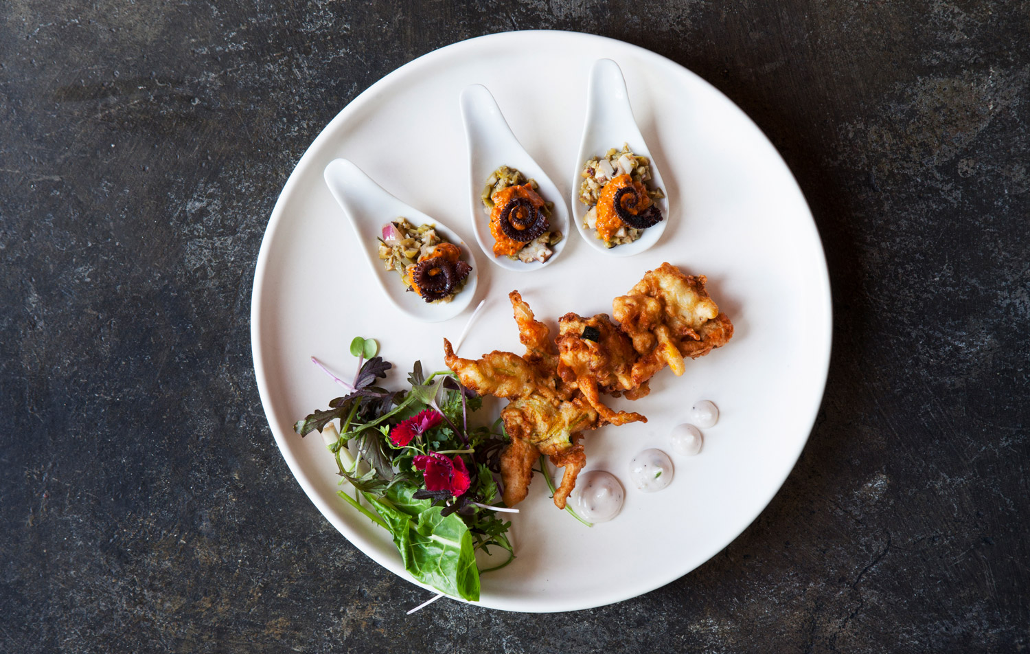 """From the """"delicious bites"""" section of the menu,  squash blossom fritters with grilled octopus and tapenade on the little spoons."""