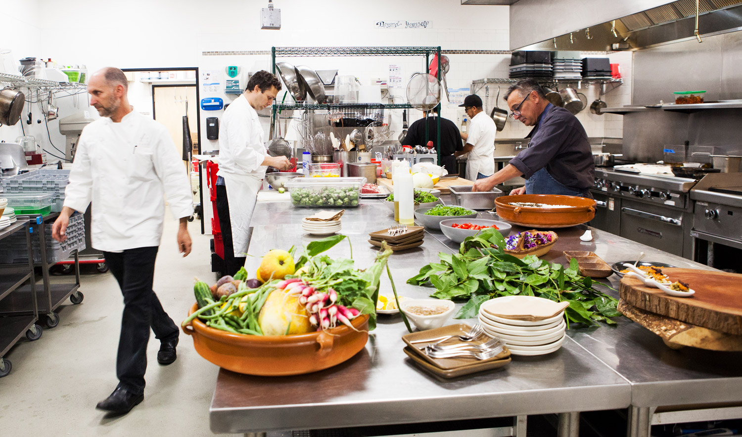 """Chef Ed Vigil (far right) prepares a few """"delicious bites"""" as Chef Arnon Oren goes out to usher the night's Anaviv's Table guests into the kitchen."""
